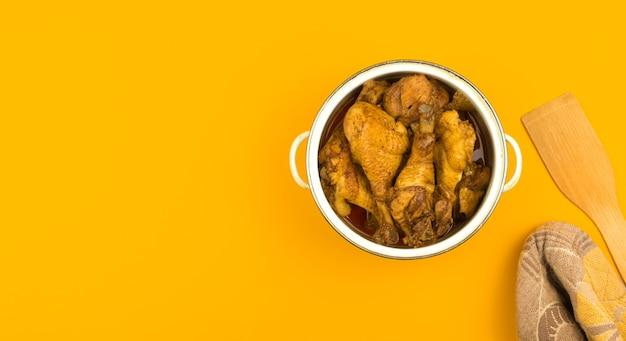 Cozinha de área de trabalho com frango frito em uma panela, coxas de frango frito para o jantar, comida para toda a família, plano de fundo colorido laranja com espaço de cópia, foto de vista superior