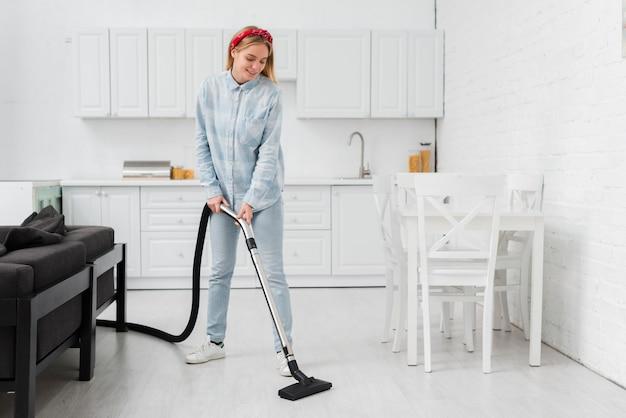Cozinha de limpeza de mulher com aspirador