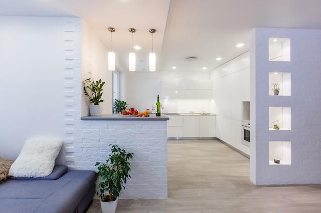 Cozinha de luxo contemporânea moderna em tons de creme com eletrodomésticos embutidos e balcão para café da manhã
