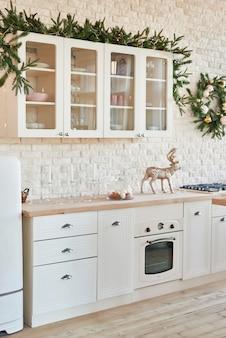 Cozinha de luz interior com decoração de natal e árvore. cozinha branca em estilo clássico. natal na cozinha. cozinha brilhante em tons de branco com o natal.