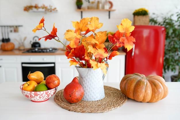 Cozinha de outono com legumes, abóbora e folhas amarelas no vaso na mesa branca.