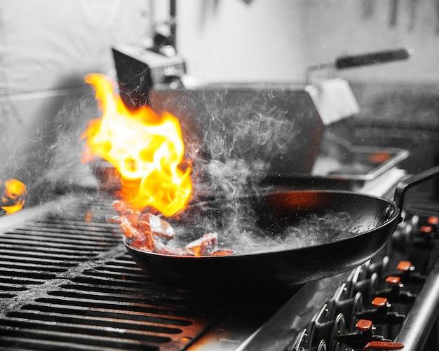 Cozinha de restaurante cozinhando comida com fogo em uma panela com fumaça