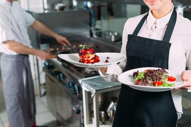 Cozinha de restaurante. empregado de mesa com um prato pronto foie gras posando na cozinha.