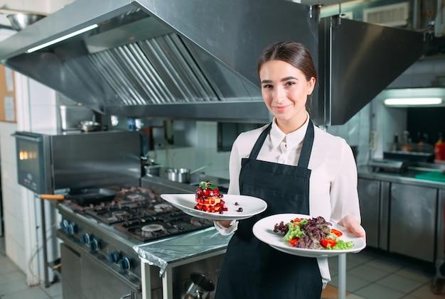 Cozinha de restaurante. empregado de mesa com um prato pronto foie gras posando no fundo da cozinha.