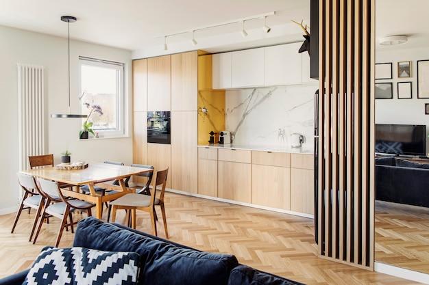 Cozinha escandinava elegante e interior da sala de jantar com mesa de família, cadeiras e acessórios