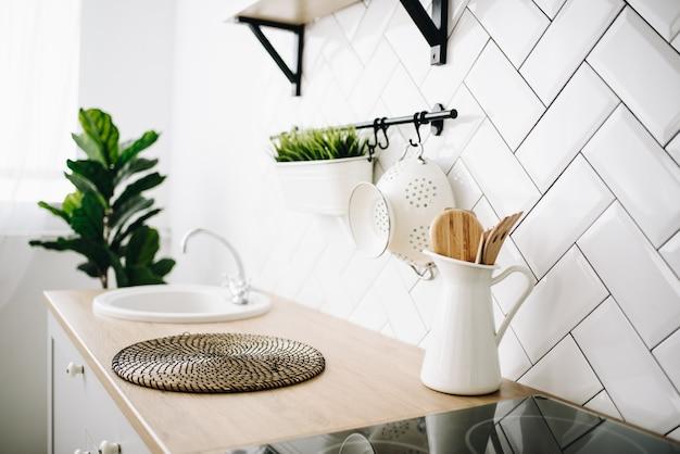 Cozinha escandinava moderna espaçosa, com ladrilhos brancos. quarto luminoso. interior moderno. pia.