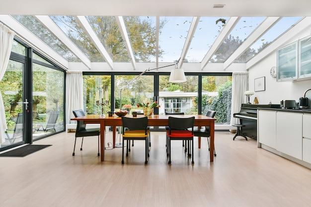 Cozinha espaçosa mansão com paredes de vidro e teto acima da mesa de jantar de madeira à luz do dia