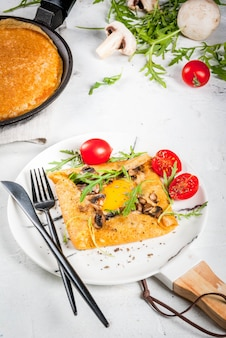 Cozinha francesa. café da manhã, almoço, lanches. comida vegana. prato tradicional galette sarrasin. crepes com ovos, queijo, cogumelos fritos, folhas de rúcula e tomate. em uma mesa de concreto branca.