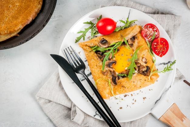 Cozinha francesa café da manhã, almoço, lanches comida vegetariana prato tradicional galette sarrasin crepes com ovos queijo cogumelos fritos rúcula folhas e tomates
