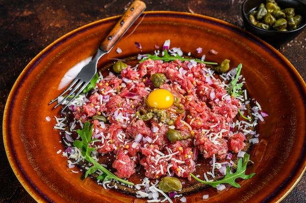 Cozinha francesa tártaro de carne com gema de ovo crua. fundo escuro. vista do topo.