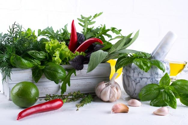 Cozinha fresca ervas e especiarias, óleo com uma argamassa de cerâmica branca. manjericão endro salada sálvia arugulagarlic pimenta