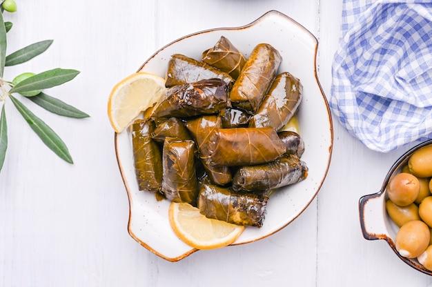 Cozinha grega tradicional. arroz embrulhado em folhas de uva. dolma com limão e especiarias. comida caseira