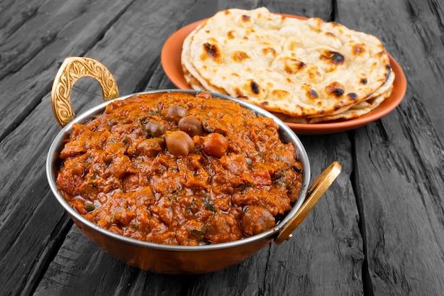 Cozinha indiana chana masala, servida com tandoori roti em fundo de madeira
