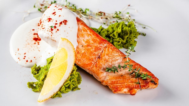 Cozinha italiana. bife de peixe vermelho, salmão com limão, um prato de espinafre. lindo restaurante que serve em um prato branco com uma taça de vinho branco