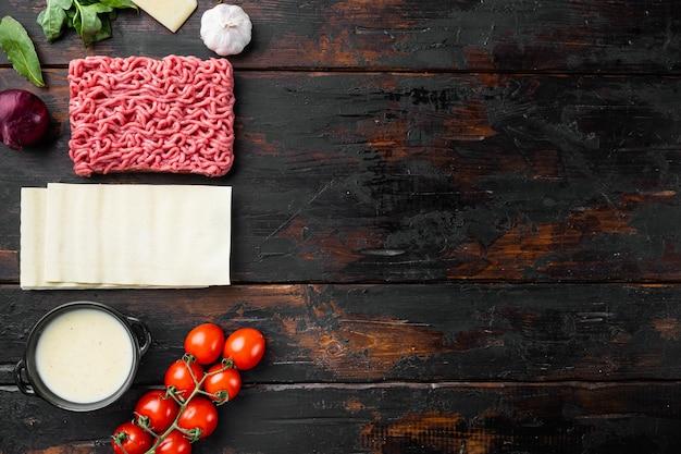 Cozinha italiana ingredientes para cozinhar alimentos com lasanha, macarrão, queijo parmesão e tempero definido na velha mesa de madeira escura vista de cima da mesa plana com espaço de cópia