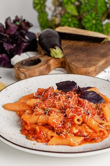 Cozinha italiana. macarrão penne com molho de tomate berinjela, manjericão roxo e queijo parmesão.
