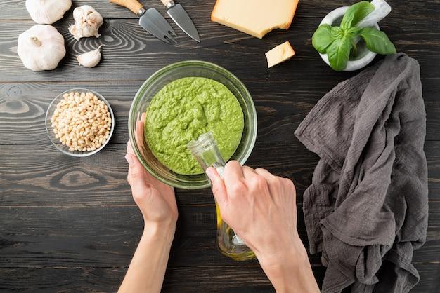 Cozinha italiana. passo a passo cozinhando molho pesto italiano. etapa 7 - adicionar um pouco de azeite. manjericão verde fresco, queijo parmesão, nozes, azeite e alho, vista superior na mesa de madeira preta