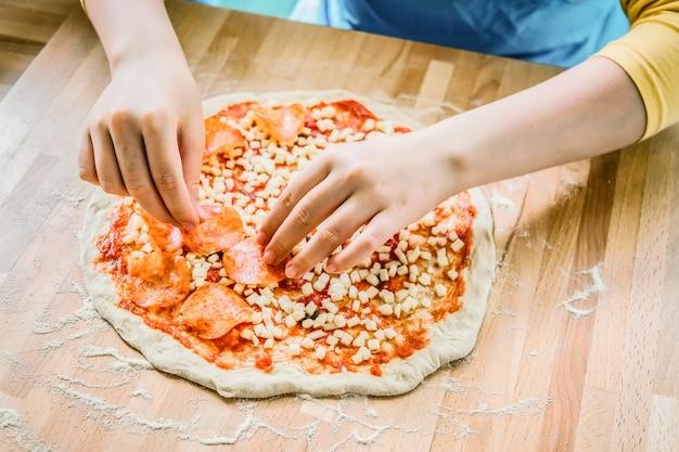 Cozinha italiana. preparação de pizza saborosa fresca. mãos femininas colocando calabresa na pizza.