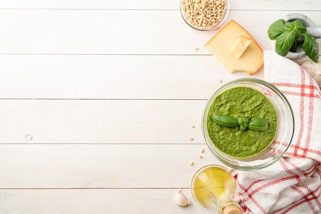 Cozinha italiana. preparando molho pesto italiano caseiro. pesto fresco em uma tigela com ingredientes, vista de cima plana deitada na mesa de madeira branca, copie o espaço