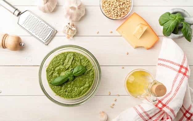 Cozinha italiana. preparando molho pesto italiano caseiro. pesto fresco em uma tigela com ingredientes, vista de cima plana e deitada na mesa de madeira branca