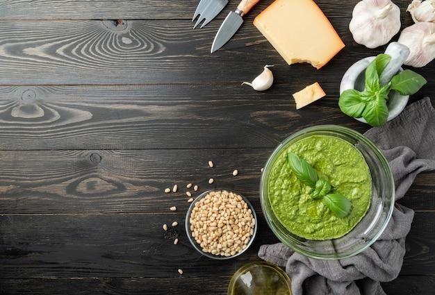 Cozinha italiana. preparando molho pesto italiano caseiro. pesto fresco em uma tigela com ingredientes, vista de cima plana e deitada na mesa de madeira preta, copie o espaço