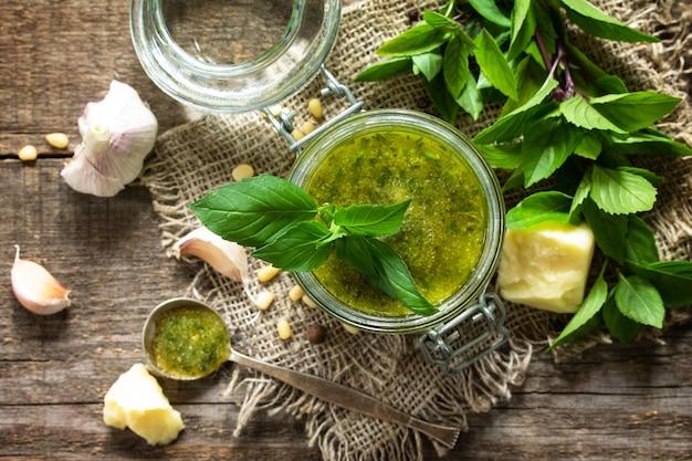 Cozinha italiana saudável molho pesto verde com ingredientes em uma mesa de madeira vista superior