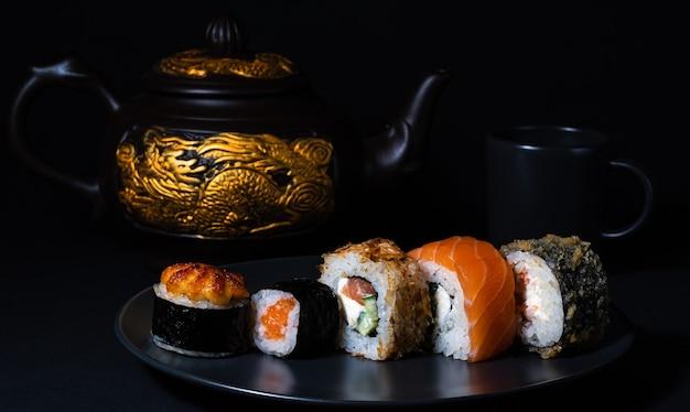 Cozinha japonesa conjunto de pãezinhos em um prato preto e um bule de chá com um dragão dourado no fundo