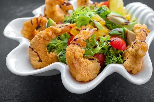 Cozinha japonesa - tempura camarão camarão em tempura com rodelas de limão e salada em fundo preto