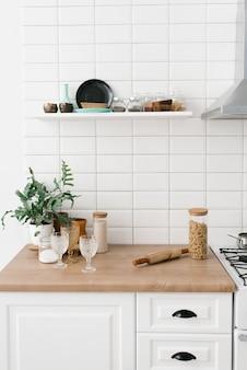 Cozinha luminosa em estilo escandinavo. macarrão em uma jarra de vidro, planta de casa, copos e utensílios de cozinha. decoração