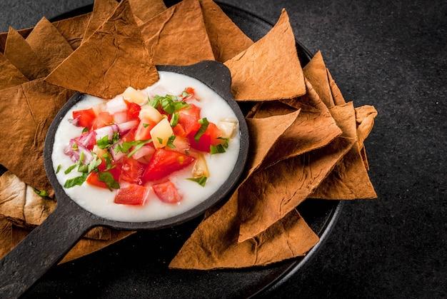 Cozinha mexicana, latino-americana. receita queso blanco - cream cheese, creme, legumes frescos, tomates, cebola, pimentão, ervas. com tortilhas assadas, mesa de pedra preta. copyspace
