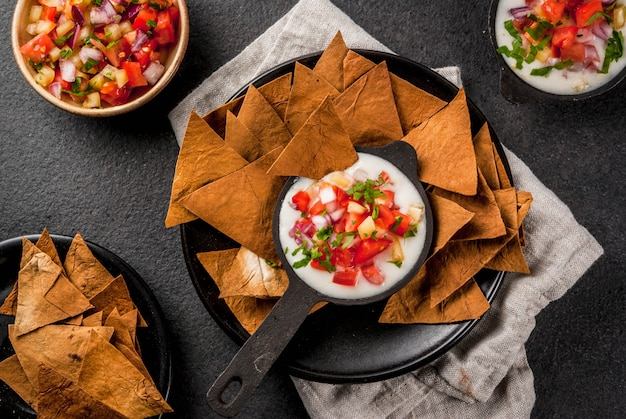 Cozinha mexicana, latino-americana. receita queso blanco - cream cheese, creme, legumes frescos, tomates, cebola, pimentão, ervas. com tortilhas assadas, mesa de pedra preta. vista superior copyspace