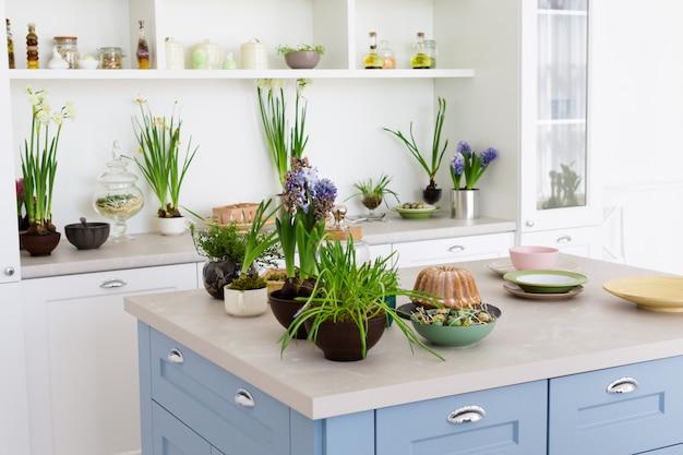 Cozinha moderna com mesa, flores verdes e bolo.
