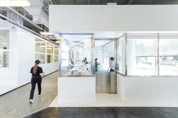 Cozinha moderna da pastelaria decorada no branco e no vidro de janela com linha de produção.