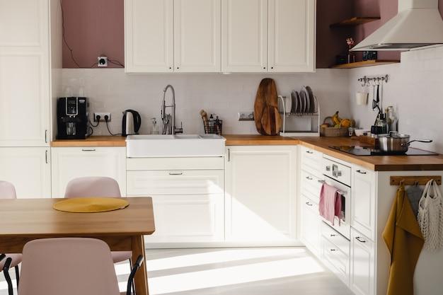 Cozinha moderna de estilo escandinavo com armários brancos, balcão de madeira e mesa de jantar com luz do sol durante o dia. conjunto completo de equipamentos de cozinha, panela, placa eléctrica, palheta, fruta.