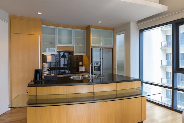 Cozinha moderna luxuosa e limpa de madeira com balcão de vidro contra janela iluminada pelo sol plano horizontal