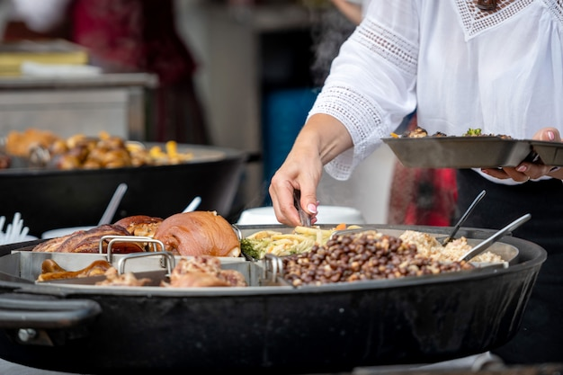 Cozinha nacional letã. uma mulher coloca pratos quentes em uma panela grande.