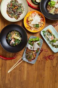 Cozinha oriental em pratos na mesa de madeira