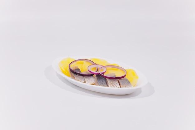 Cozinha russa na forma de batatas com endro e arenque em um prato branco close-up
