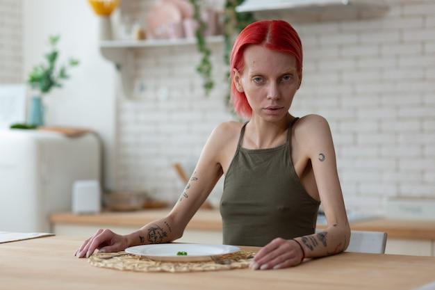 Cozinha sozinha. mulher ruiva anoréxica com uma aparência horrível sentada sozinha na cozinha