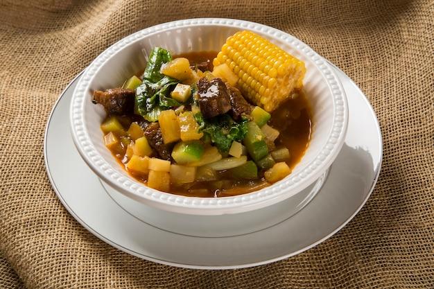 Cozinha sul-americana: sopa de puchero com grão de bico em panela sobre a mesa.