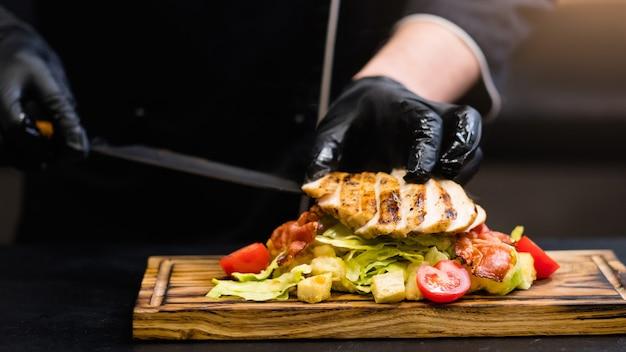 Cozinha tradicional italiana. chef fazendo salada caesar com filé de frango defumado, chips de bacon e vegetais.