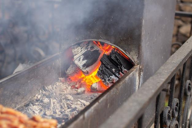 Cozinhamos muitos kebabs na grelha. as brasas acesas. espetadas amarradas em espetos de madeira em um café de rua. o processo de cozinhar kebabs com muita fumaça.