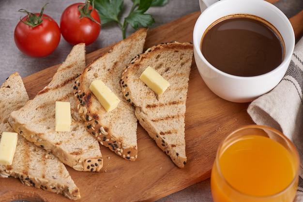 Cozinhando café da manhã tradicional. close up tiro. manteiga e pão no café da manhã, xícara de café e suco de laranja.
