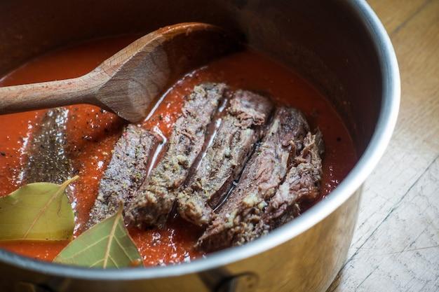 Cozinhando carne tenra com molho de tomate
