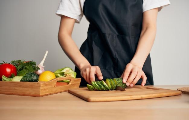 Cozinhando comida comida saudável cozinha avental preto cortando vegetais