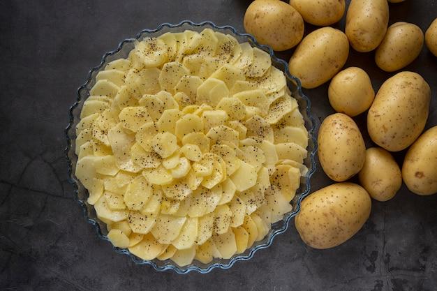 Cozinhando. cozinhar batatas assadas no forno. caçarola de batata, fatias de batatas frescas colocadas em uma assadeira. produzir.