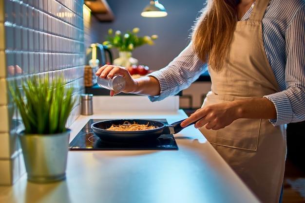 Cozinhando, dona de casa, mulher, salgando e preparando comida em uma frigideira no fogão para o jantar na cozinha moderna em estilo loft