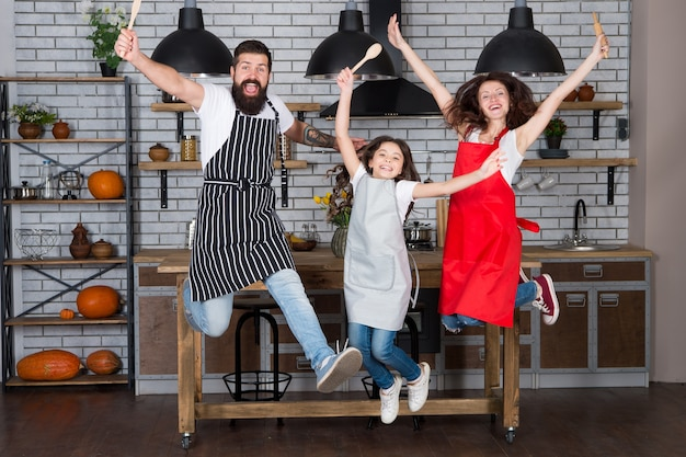 Cozinhando feliz. mãe e pai com a filha. menina com os pais no avental. dia da família. pai, mãe e filho chef cozinhando. família feliz na cozinha. manhã feliz em família. felicidade.