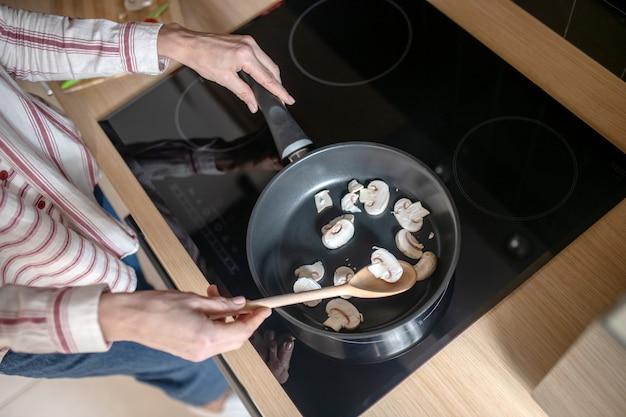 Cozinhando. foto aproximada de uma dona de casa mexendo comida em uma frigideira
