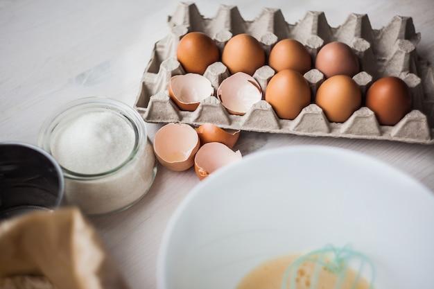 Cozinhando ingredientes para a massa e a pastelaria, ovos, farinha na madeira rústica branca.
